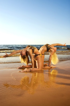 Two acrobatic girl on the beach (reflected in water) photo