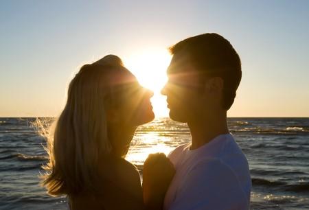 besos apasionados: Abrazos joven, disfrutando de la puesta de sol de verano. Foto de archivo