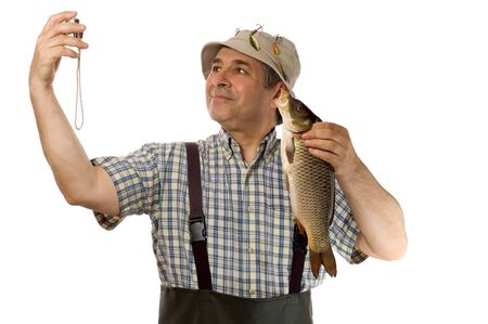 Senior fisherman with his catch (isolated on white) photo