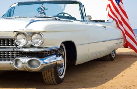 Classic white car at the beach with American flag