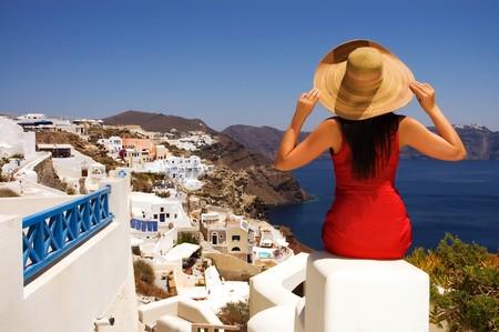 greek islands: Beautiful young Greek woman on the streets of Oia, Santorini, Greece. Stock Photo