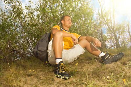 Young man hiker relaxing on the hill photo