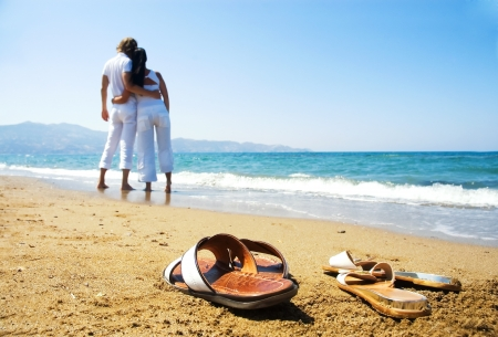 young lovers: Young attractive couple at the beach (focused front view)