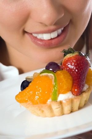 Young woman with low-calorie fruit cake (focus on face) photo