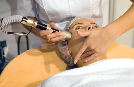 Young woman getting skin cleaning at beauty salon photo