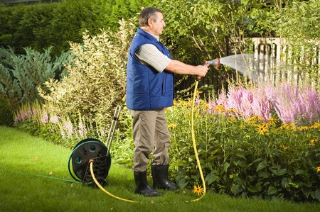 Senior man watering flowers in the garden