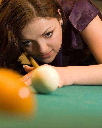 Beautiful young woman playing billiards photo
