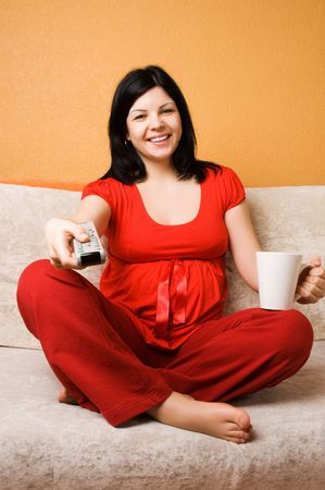 Beautiful pregnant woman sitting on the couch photo