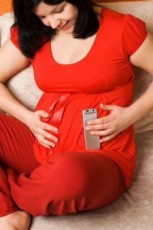 Pregnant woman with mobile phone photo
