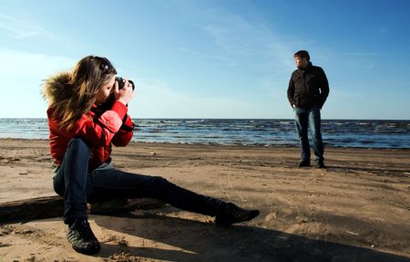Young woman taking a photo of her boyfriend on the beach (Woman in focus) photo