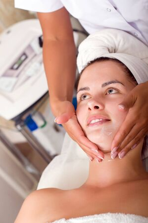 Young woman getting skin cleaning at beauty salon (shallow dof) photo