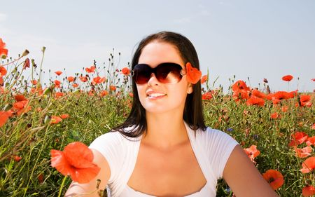 Young beautiful woman in poppy flowers photo