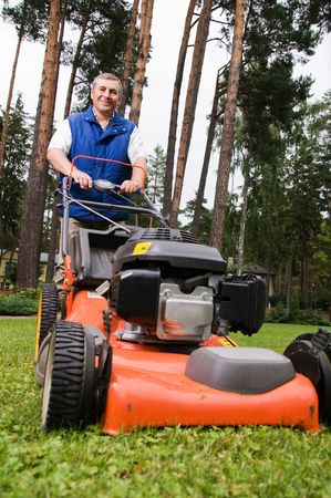 cut grass: Senior man mowing the lawn. Stock Photo