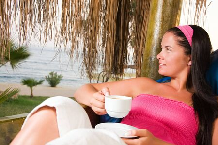 Young woman having a cup of coffee in bungalow Stock Photo - 5490659