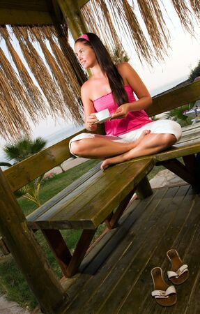 Young woman having a cup of coffee in bungalow Stock Photo - 5490677