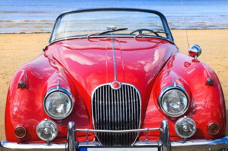 coche antiguo: Viejo coche rojo cl�sico en la playa Foto de archivo
