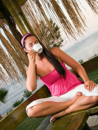 Young woman having a cup of coffee in bungalow