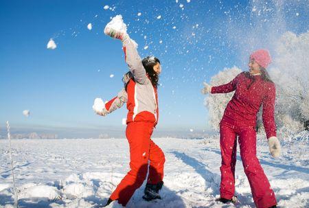 ni�as jugando: Dos ni�as jugando con la nieve Foto de archivo