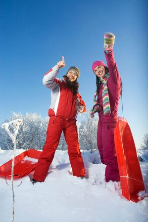 Two young beautiful girls with sledges photo