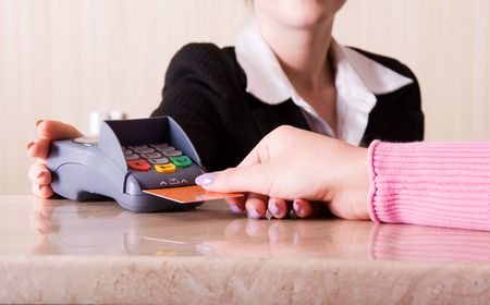 Close-up of woman hand holding credit card in payment terminal photo