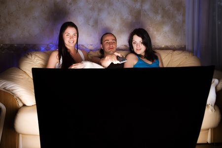 Three friends are watching TV  photo