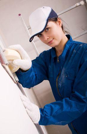 Young woman builder polishing the wall  photo