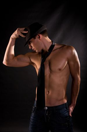sexy male model: Dramatic light photo of muscular young man in front of black background Stock Photo