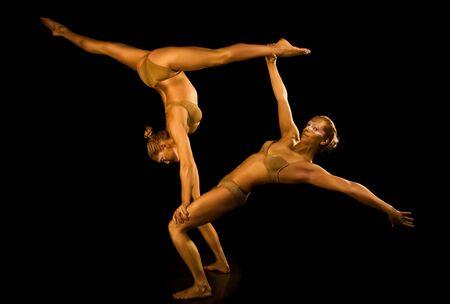 akrobatik: Zwei akrobatischen M�dchen Muskeltrainings in gold Lizenzfreie Bilder