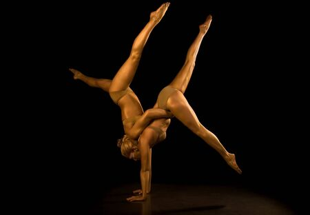 acrobat: Two acrobatic girl toned in gold