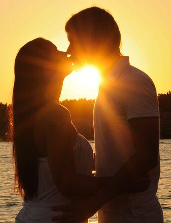 besos apasionados: Par abrazos, disfrutar de la puesta de sol del verano.  Foto de archivo