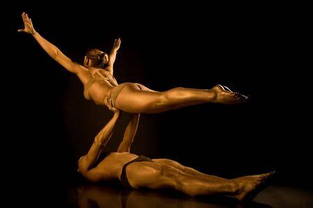 bailarin hombre: Dos acróbatas tonificados en oro  Foto de archivo