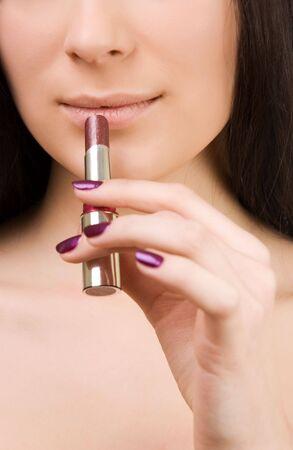 Young beautiful brunette girl holding lipstick   photo