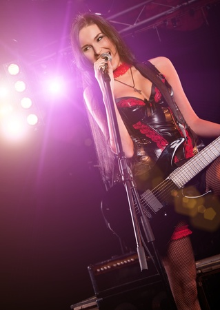 Glamorous girl holding a guitar and singing on the stage Stock Photo - 8341286