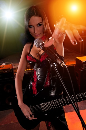 Glamorous girl holding a guitar and singing on the stage photo