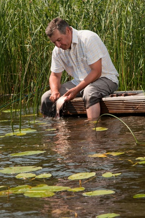 Senior man scaling fish Stock Photo - 8341346