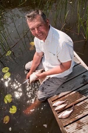 Senior man scaling fish photo