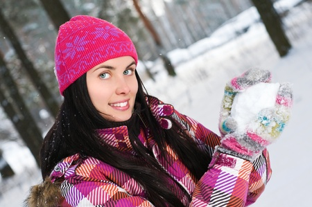 Beautiful young woman outdoor in winter playing with snow photo