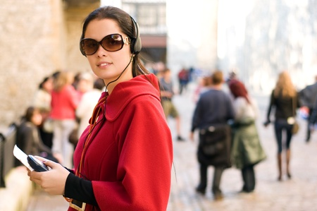 Young woman with headphones, listening to audio guide  Stock Photo