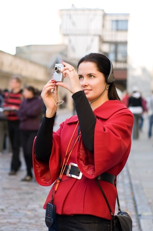 Young woman with headphones, listening to audio guide taking pictures photo