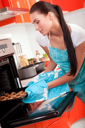 Beautiful brunette woman in the kitchen baking cookies. photo