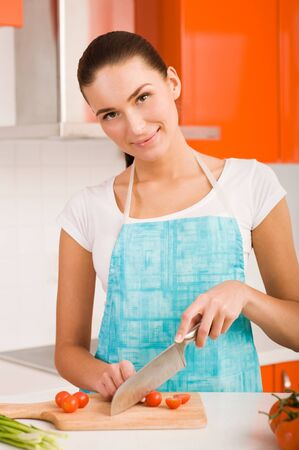Young woman cutting vegetables in a kitchen  photo