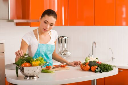 Woman cutting vegetables in modern kitchen interior  photo