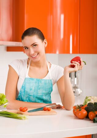 Young woman cutting vegetables in modern kitchen interior  photo