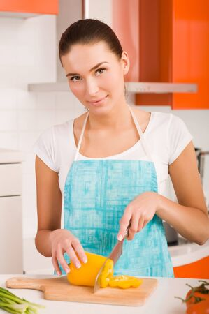 Woman cutting vegetables in a kitchen  photo