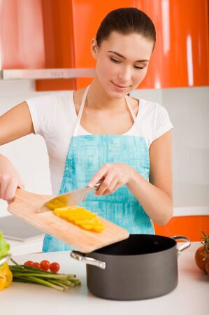 Beautiful young woman cooking in the kitchen Stock Photo - 9183573