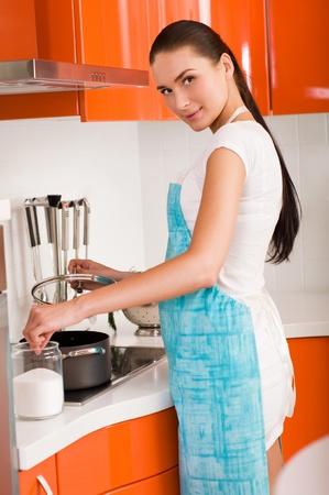ama de casa: Joven y bella mujer cocina en la cocina Foto de archivo