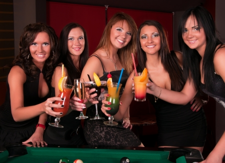 Group of happy girls drinking cocktails photo
