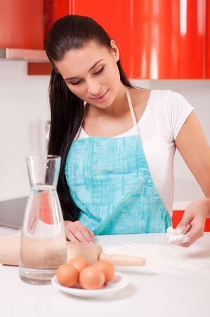 Woman mixing flour on the table photo