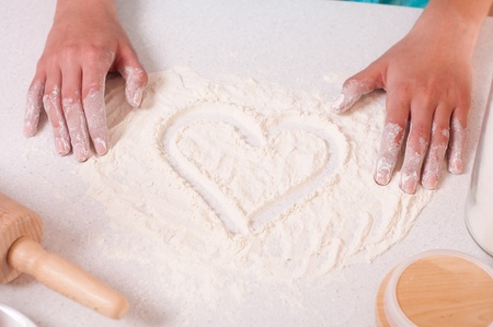 Heart shape on flour, done by woman hands. Stock Photo - 11854245