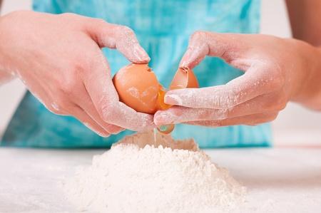beaten woman: Woman hands breaking egg into flour